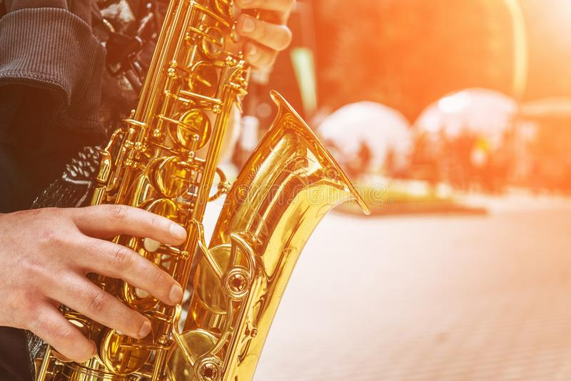 Конец-вверх руки музыканта улицы играя саксофон стоковая фотография