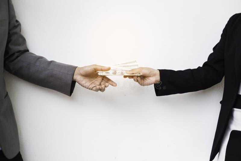 Конец-вверх руки персоны давая деньги к другой руке стоковое фото