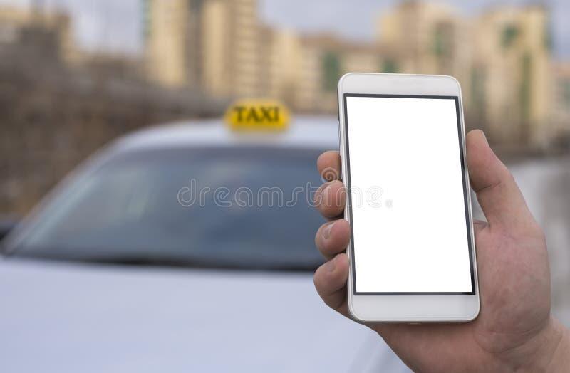 Конец-вверх руки человека держа мобильный телефон на заднем плане автомобиля и города стоковое фото rf