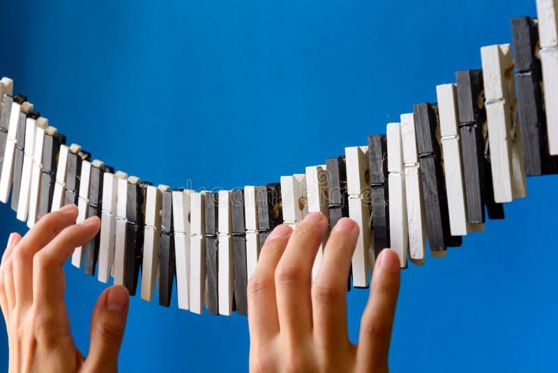 Конец-вверх руки ` s женщины играя мнимый рояль сделанный от штырей одежд на предпосылке голубой бумаги стоковая фотография rf