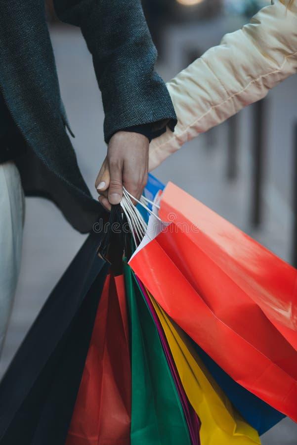 Конец-вверх рук держа хозяйственные сумки стоковое изображение rf