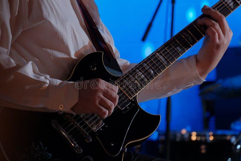 Конец-вверх рук музыканта который держит гитару Гитарист играет электрическую гитару белизна утеса музыканта человека предпосылки стоковые фото