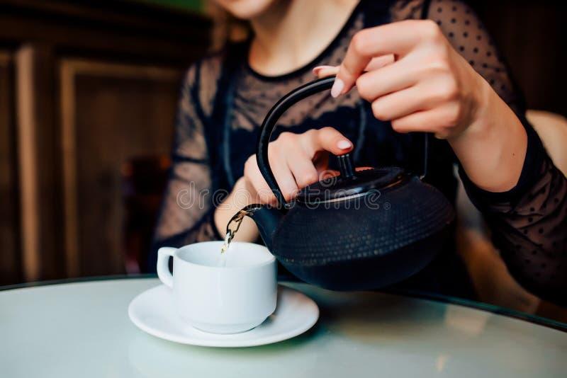 Конец вверх рук счастливой девушки имеет чашку зеленого чая стоковые фотографии rf
