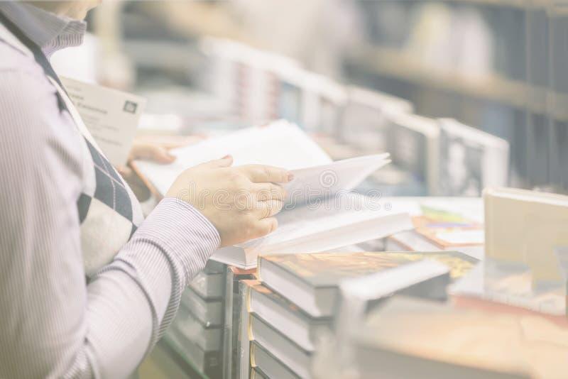 Конец-вверх рук ` s женщины с много интересными книгами, bookstore Образование, школа, исследование, читая концепцию небылицы стоковые изображения