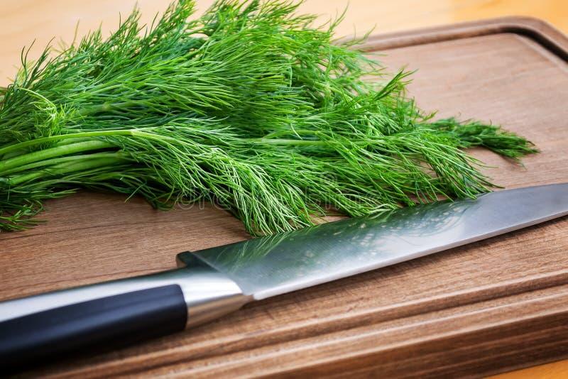 Конец-вверх свежего зеленого укропа и острого профессионального ножа шеф-повара на коричневой деревянной разделочной доске Свежие стоковое изображение rf