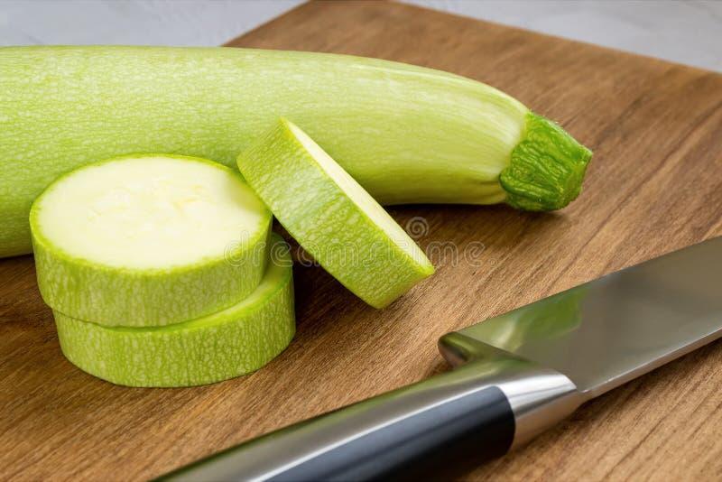 Конец-вверх свежего зеленого цукини, немногих кусков и ножа шеф-повара на коричневой деревянной разделочной доске Сварите дома Св стоковое фото