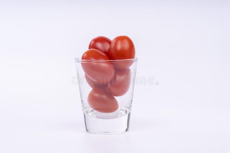 Конец вверх свежих томатов вишни в ясном стеклянном стоге изолированном на белой предпосылке с путем клиппирования стоковые изображения