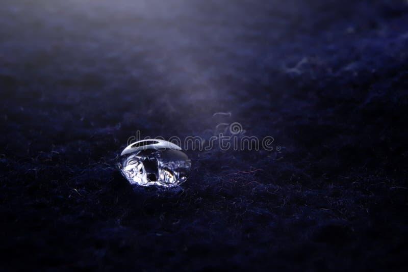 конец-вверх сверкная падения воды на светящих синих шерстях boild - яркое светлое настроение с глубокими тенями стоковая фотография rf