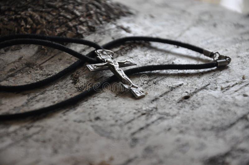 конец-вверх серебряного правоверного креста лежа на коре березы стоковое изображение rf