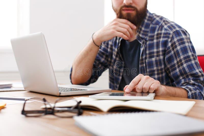Конец вверх серьезного работника офиса человека читает отчет, пока сидит на таблице с открытой сет-книгой стоковая фотография rf