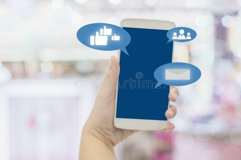 Конец-вверх смартфона в женщинах держа руки показывая зону в торговом центре, концепцию знака сигнала WiFi удобства в покупках стоковое фото