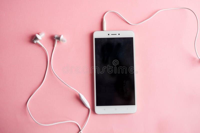 Конец-вверх смартфона с наушниками на розовой предпосылке над взглядом слушает нот к стоковое фото