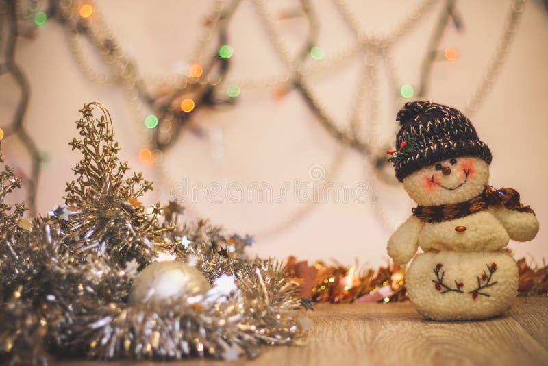 Конец-вверх снеговика на предпосылке расплывчатой покрашенной сусали светов и С Новым Годом! стоковые изображения