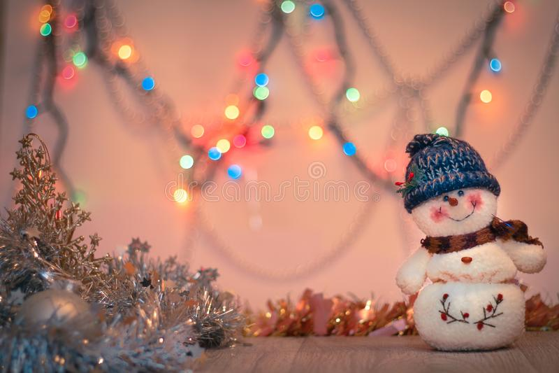 Конец-вверх снеговика на предпосылке расплывчатой покрашенной сусали светов и С Новым Годом! стоковое фото rf