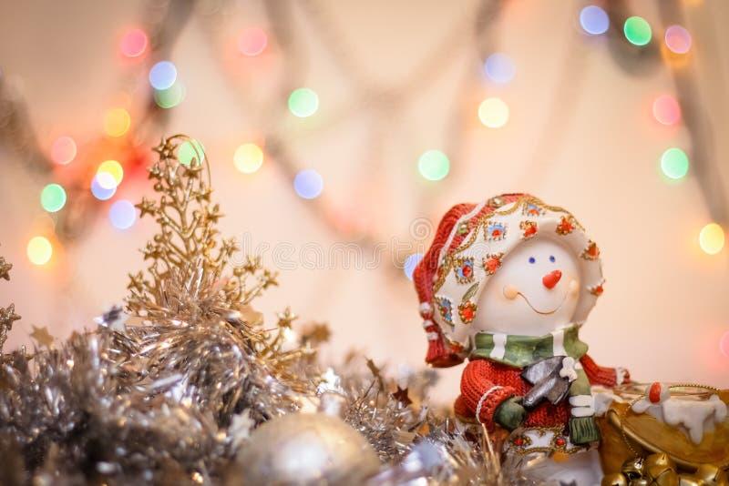 Конец-вверх снеговика на предпосылке расплывчатой покрашенной сусали светов и С Новым Годом! стоковая фотография rf