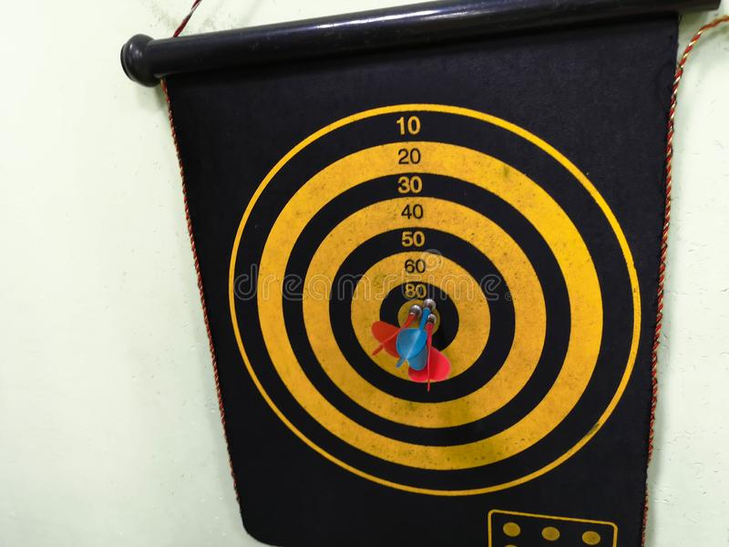 Конец вверх снял доски дротика Стрелка дротиков госпож цель на доске дротика во время игры Желтый цвет дротиков стоковое фото rf
