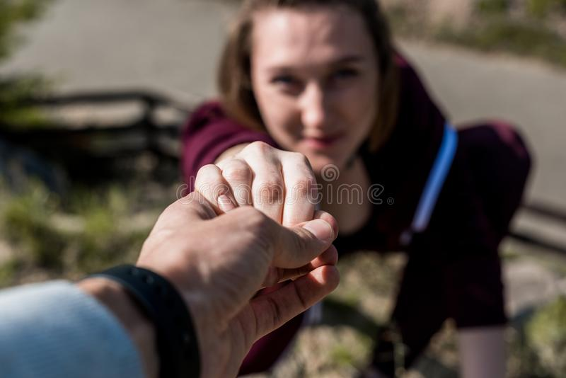 конец-вверх снял человека давая руку помощи к молодой женщине стоковые фото