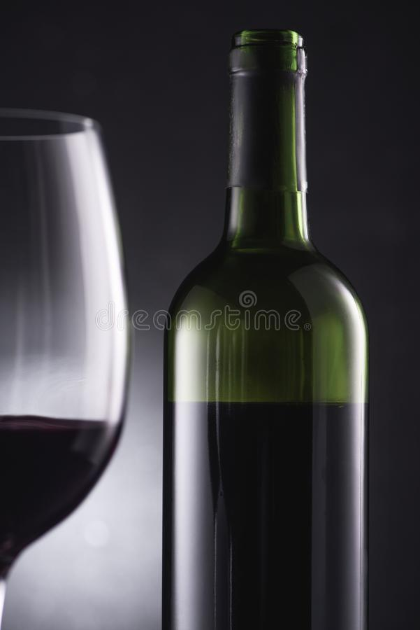 конец-вверх снятый запачканного стекла заполненного с красным вином на бутылке переднего плана и вина стоковое фото