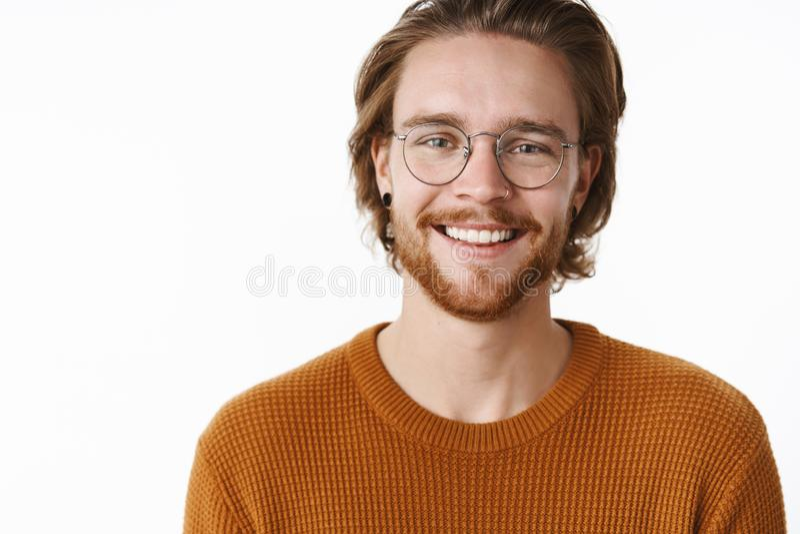 Конец-вверх снятый удовлетворенного европейского бородатого парня redhead в стеклах с зелеными глазами нося свитер усмехаясь широ стоковые фотографии rf