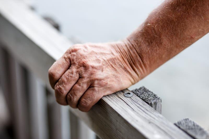 Конец-вверх старика стоя около деревянной загородки пока кладущ руку на прокладывать рельсы стоковые изображения rf