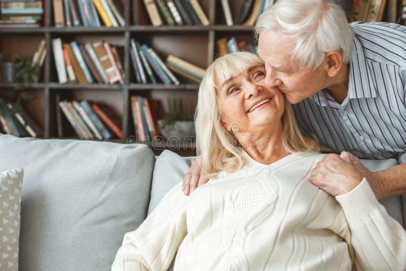 Конец-вверх старшей пар концепции выхода на пенсию совместно дома целуя стоковые изображения