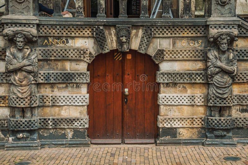Конец-вверх статуй вокруг лесистой двери перед готическим зданием здание муниципалитета гауда в пасмурном дне стоковые изображения rf