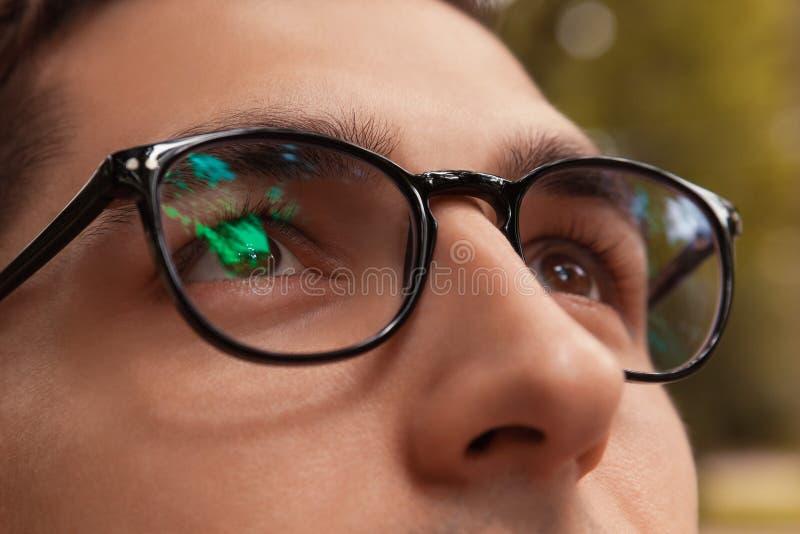 Конец-вверх стекел человека нося Брайн-наблюданный парень смотря вверх Здоровая концепция визирования Бизнесмен, студент в eyewea стоковое изображение rf