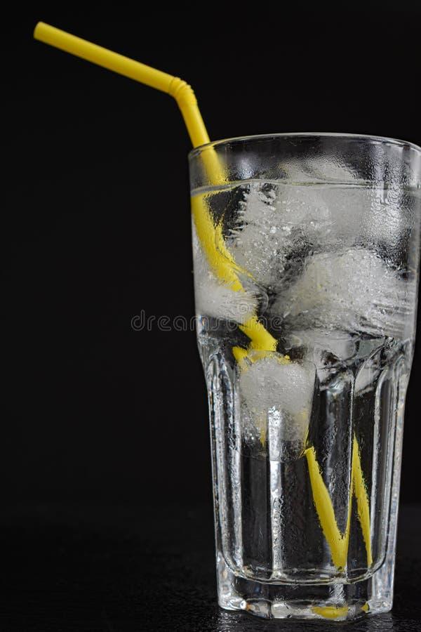 Конец-вверх стеклянной чашки с водой, много кубов льда и желтой соломой на черной предпосылке стоковые изображения rf