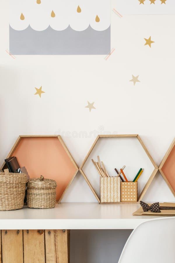 Конец-вверх стола с чашками ручки, полками в форме honeyc стоковые изображения rf