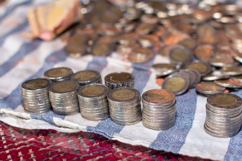 Конец-вверх 9 строк монеток штабелированных рядом с много разбросанными на таблицу стоковое изображение rf