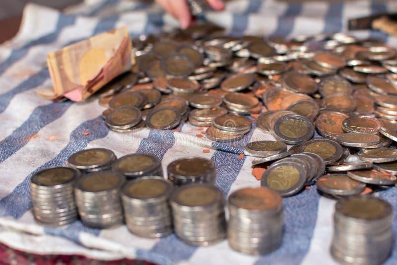 Конец-вверх строк штабелированных монеток рядом с много монеток разбросанных на таблицу и банкноту стоковое фото