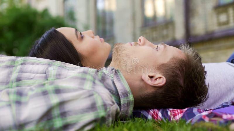 Конец-вверх счастливых пар лежа на траве и наслаждаясь датой, влюбленностью и поддержкой стоковая фотография rf