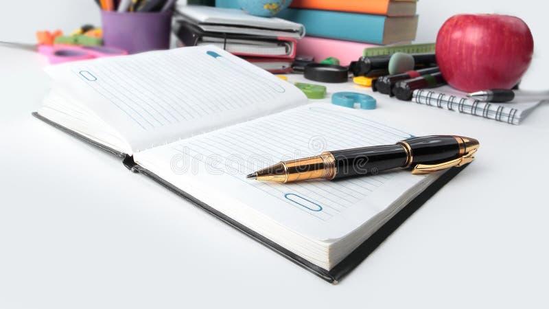 конец вверх тетрадь, ручка и школьные принадлежности изолированные на белой предпосылке Фото с космосом экземпляра стоковые изображения rf