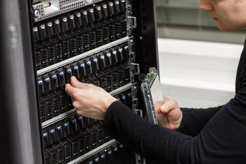 Конец-вверх техника мужчины ИТ анализируя САН в Datacenter стоковое фото