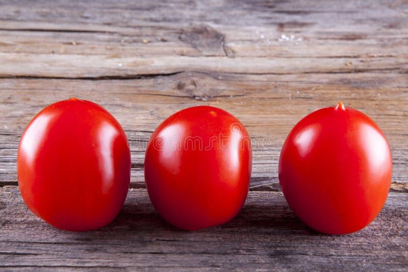 Конец-вверх томатов на древесине стоковые изображения rf