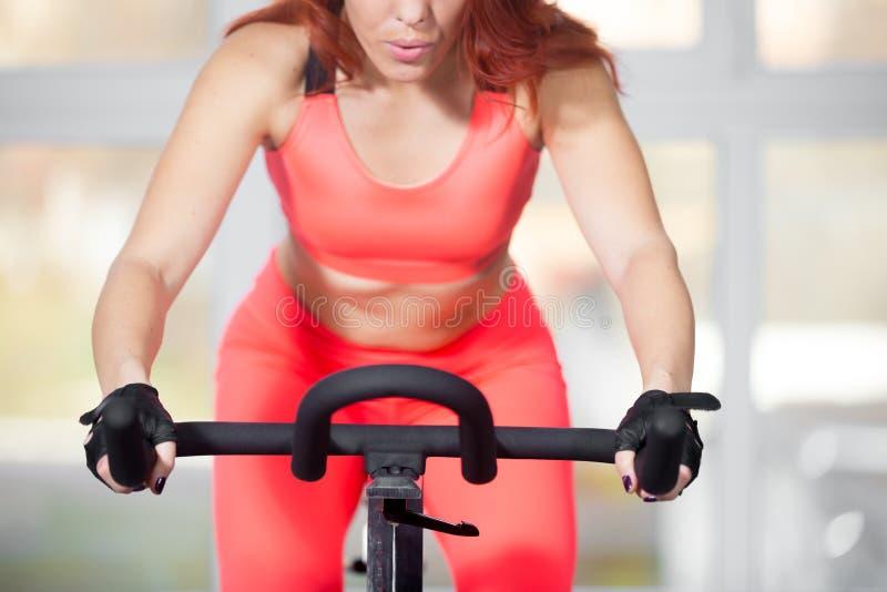 Конец-вверх, тренировка женщины на задействуя машине в фитнес-центре стоковые изображения rf