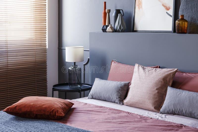 Конец-вверх угла темного интерьера спальни при включении лампа A.M. стоковое фото rf