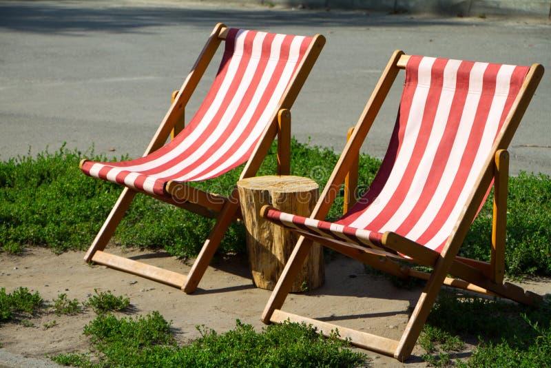 Конец-вверх 2 удобных красных и белых кресел для отдыха в парке и пне между ими стоковое изображение
