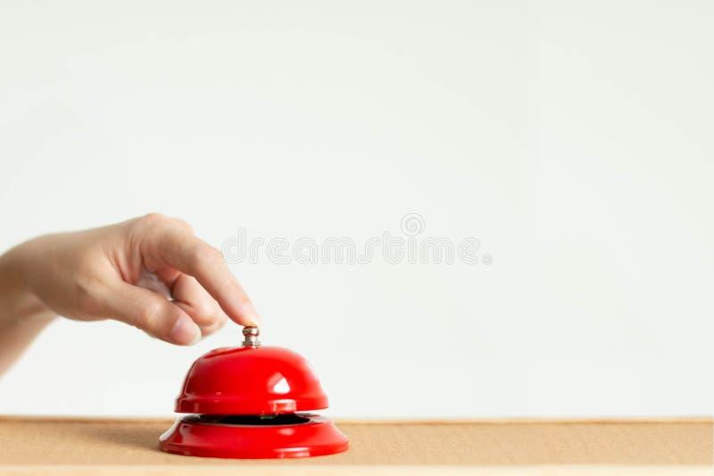 Конец-вверх указательного пальца отжимая кнопку колокола красного винтажного колокольчика стиля на деревянном столе стоковое фото