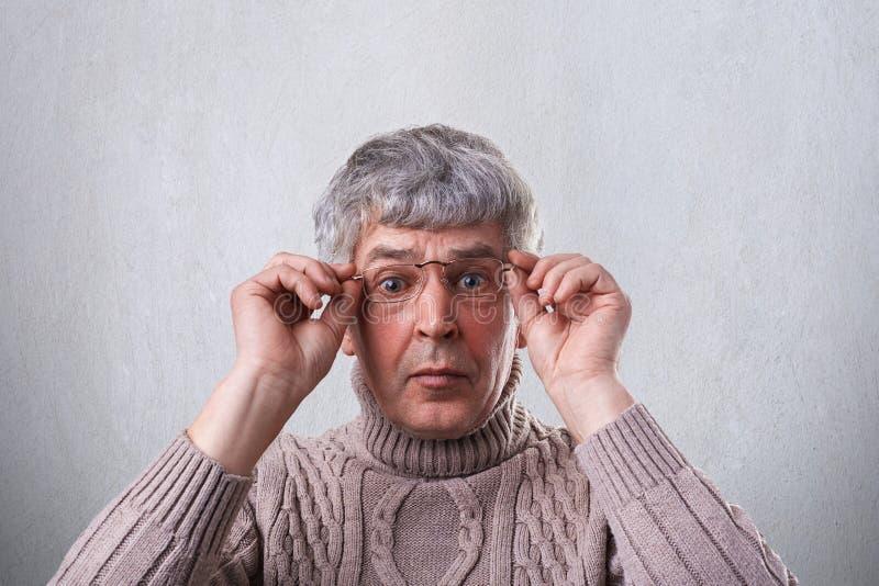 Конец-вверх удивленных стекел и свитера старшего человека нося держа его руки на рамках стекел смотря с широким opene стоковые изображения