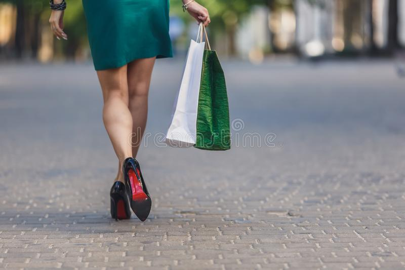 Конец-вверх хозяйственных сумок нося молодой женщины пока идущ вдоль улицы Ноги женщины сексуальные с сумкой E стоковые изображения rf