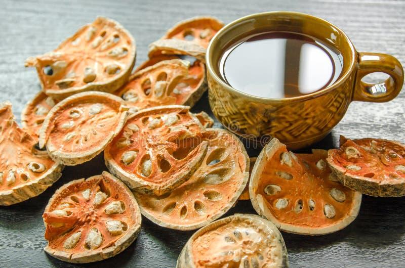 Конец-вверх чая bael сухих и стеклянных и сока bael на деревянном поле стоковая фотография