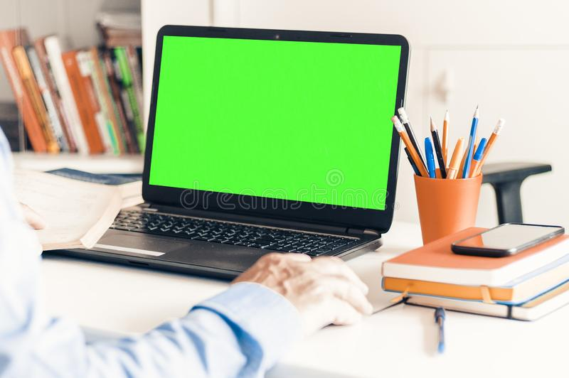 Конец-вверх человека руки используя мышь и печатать на зеленом ноутбуке экрана на белой таблице, концепции дела стоковые изображения rf