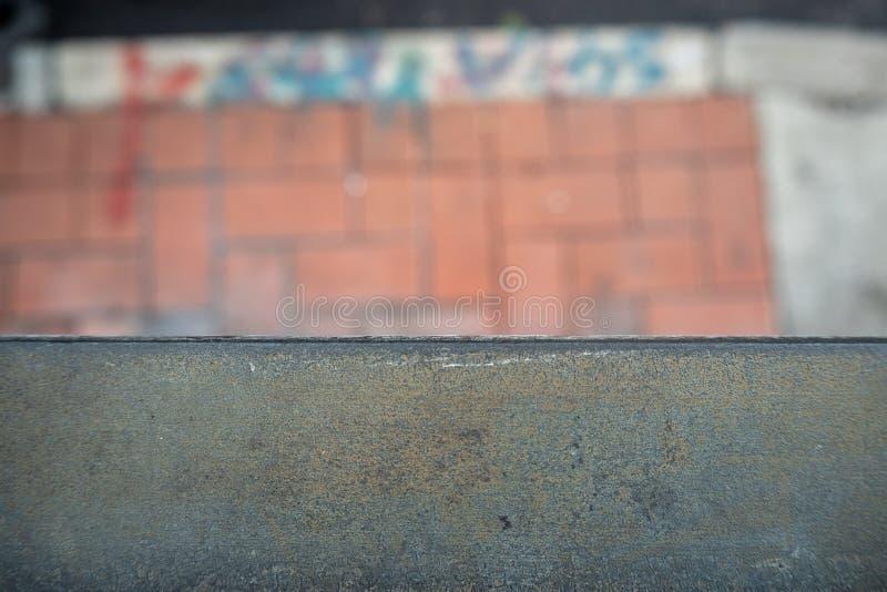 Конец-вверх черного стального рельса на запачканной пешеходной предпосылке стоковое фото