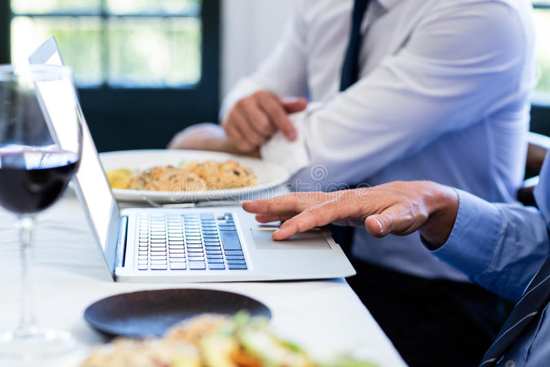 Конец-вверх человека используя компьтер-книжку во время встречи бизнес-ланча стоковая фотография