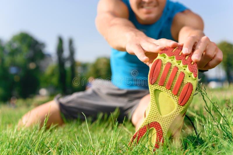 Конец-вверх человека протягивая его ногу стоковые фотографии rf