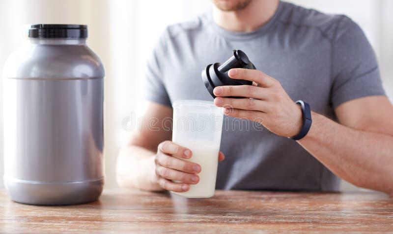 Конец вверх человека с бутылкой и опарником встряхивания протеина стоковые изображения