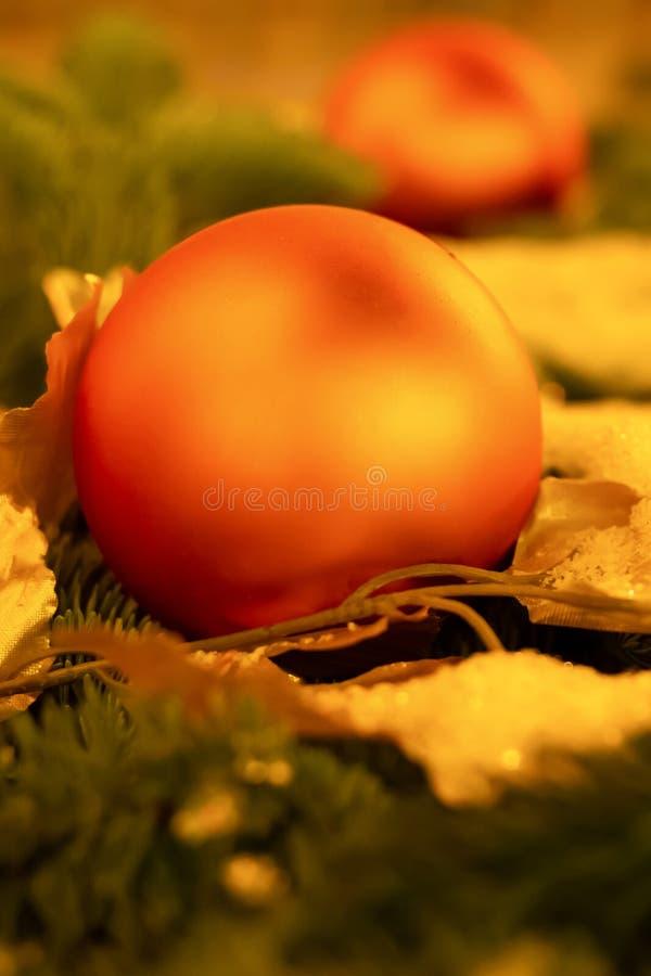 Конец-вверх шарика праздничного украшения рождества оранжевый красный покрытой снег елевой ветви стоковая фотография rf