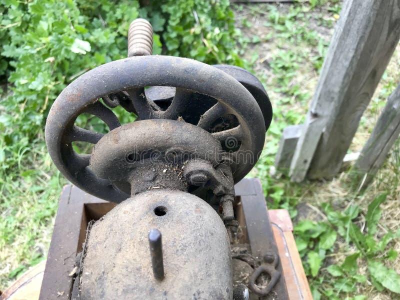 Конец-вверх швейной машины ручного привода старый Покрытый с корозией, пылью и паутинами На фоне деревянного покинутого бара стоковое фото rf