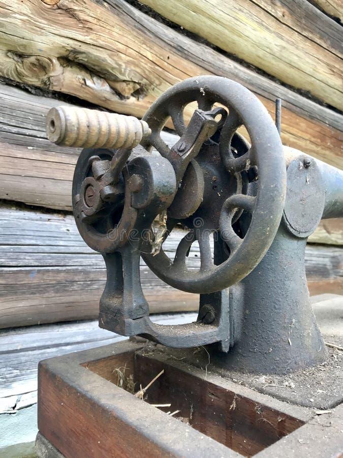 Конец-вверх швейной машины ручного привода старый Покрытый с корозией, пылью и паутинами На фоне деревянного покинутого бара стоковое изображение rf